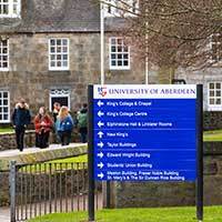 A sign with building names in front of a traditional building on the University of Aberdeen campus