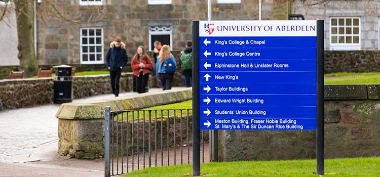 A sign with building names on it, in front of a traditional building on the University of Aberdeen campus
