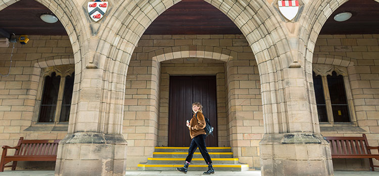 An international student walking on campus at the University of Aberdeen