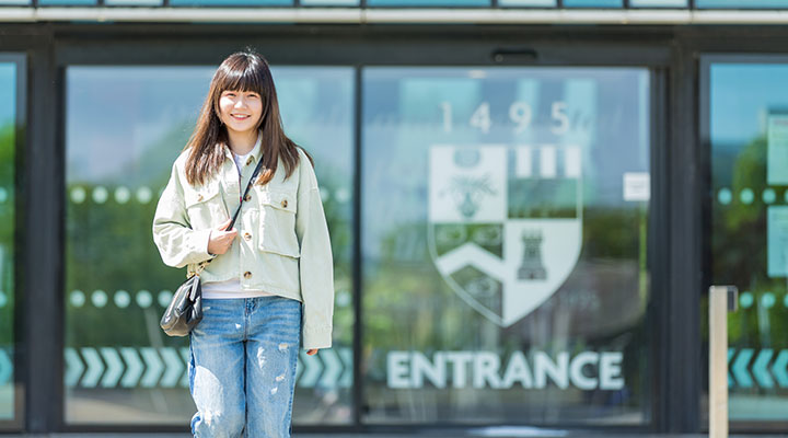 An international student in front of the Sir Duncan Rice Library at the University of Aberdeen