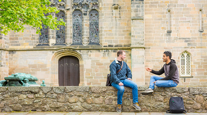 Two students sat on a wall on campus at the University of Aberdeen