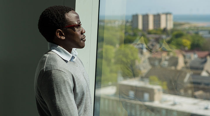 An international student looking out of the windows at the Sir Duncan Rice library at the University of Aberdeen