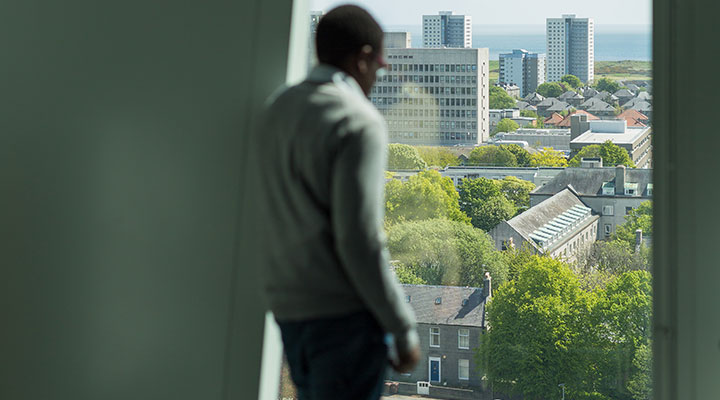 An international student looking out of the window at Sir Duncan Rice Library at the University of Aberdeen