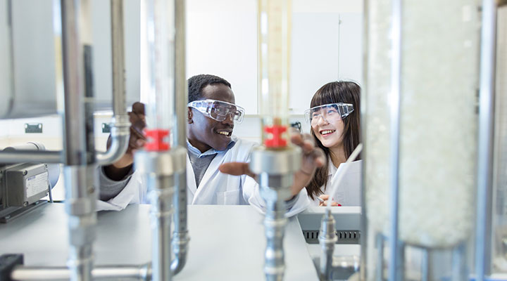 Two students smiling in a science laboratory