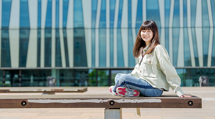 Student sat on a bench outside of the University